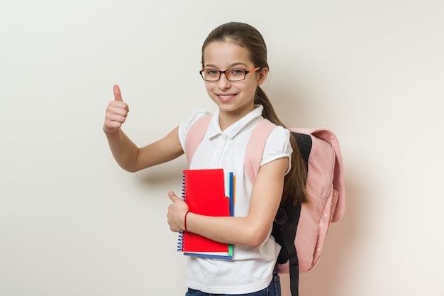 Estudante de escola menina mostrando os polegares para cima o sinal
