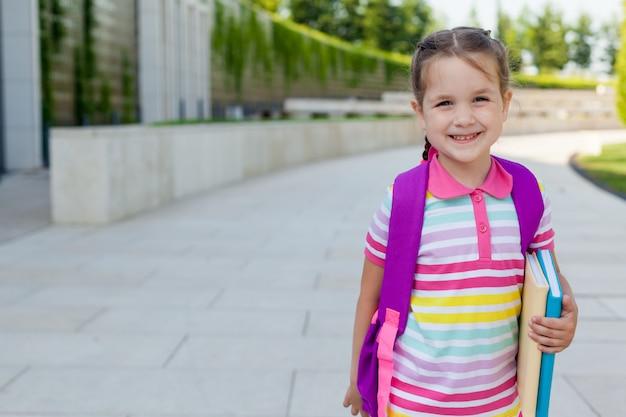 Estudante de escola primária de menina criança feliz corre para a aula.