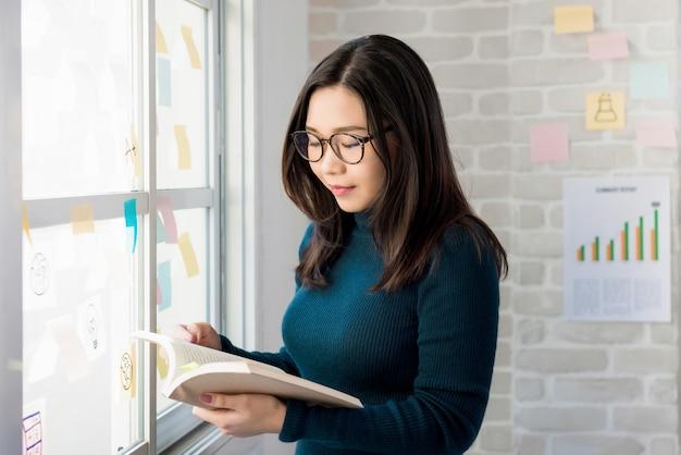 Estudante de faculdade asiática feminino lendo livro pela janela