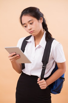 Estudante de faculdade asiática tailandesa. retrato educacional de uma estudante universitária séria e estressada carregando uma mochila e um tablet