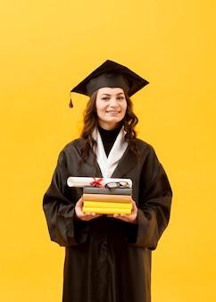 Estudante de graduação com diploma e livros