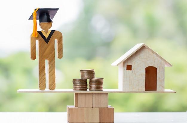 Estudante de graduação, moedas e casa no balanço de madeira. conceito de estudo requer economia de custos
