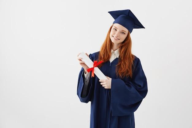 Estudante de graduação ruiva feminino com diploma sorrindo. copyspace.