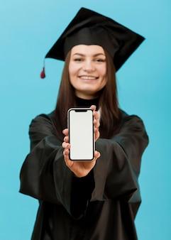 Estudante de graduação sorridente com telefone