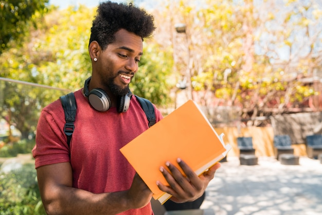 Estudante de homem afro estudando e lendo seu livro.