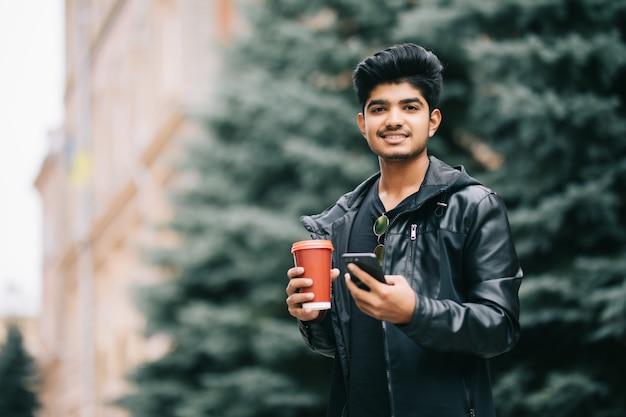 Estudante de homem bonito com óculos conversando com amigos no celular, desfrutando de café urbano enquanto caminhava na rua