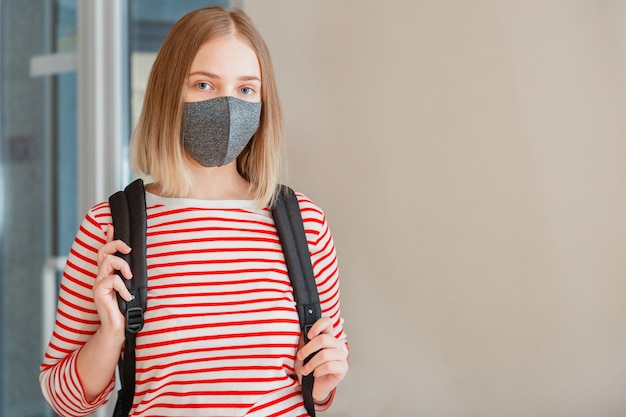 Estudante de jovem com máscara médica protetora. retrato de estudante loira garota na universidade durante o bloqueio covid coronavírus com espaço de cópia.
