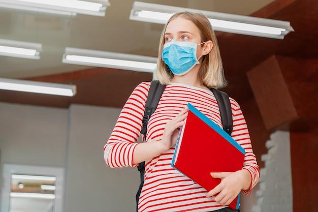 Estudante de jovem com máscara médica protetora. retrato de uma aluna loira no interior da universidade durante o bloqueio do coronavírus covid 19