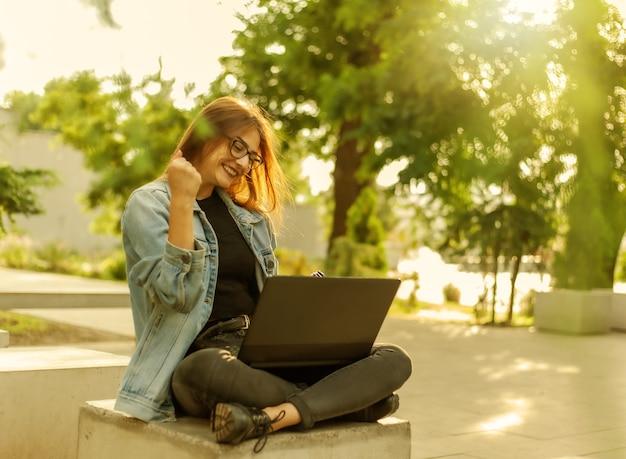 Estudante de jovem mulher feliz em uma jaqueta jeans, sentado no parque e olha para a tela do laptop. ensino à distância. chamada online. conceito moderno da juventude.