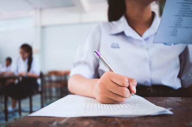 Estudante de leitura e escrita de exame com estresse em sala de aula.