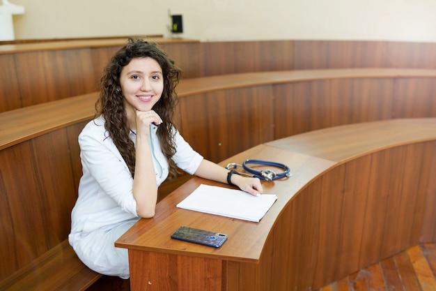 Estudante de medicina com estetoscópio e telefone olhando para a câmera