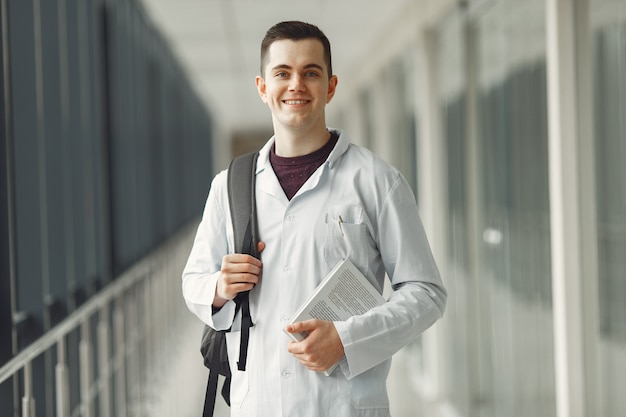 Estudante de medicina com uma mochila está de pé em uma clínica moderna