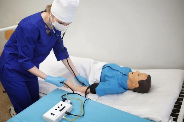 Estudante de medicina mede a pressão arterial em um manequim. treinamento em prática médica no hospital de treinamento