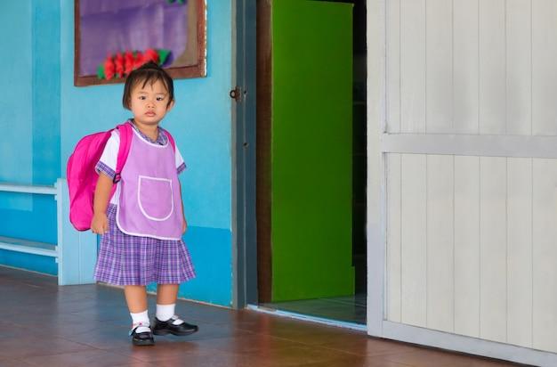 Estudante de menina asiática pré-escolar em geral uniforme e vermelho saco indo para a escola