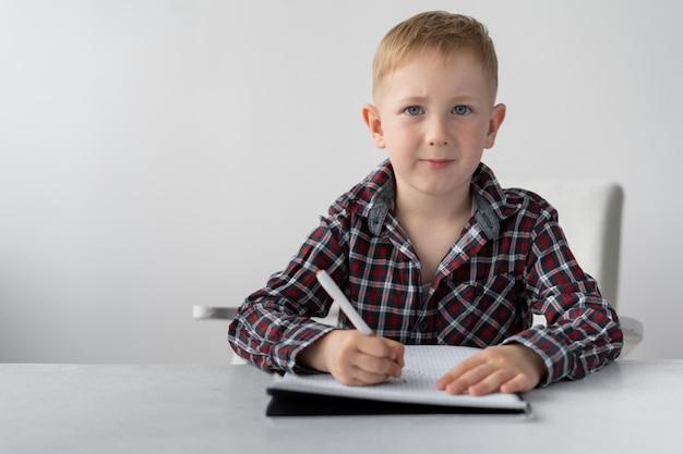 Estudante de menino faz lição de casa em quarentena em casa.