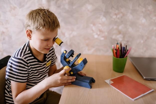 Estudante de menino olha através do microscópio em casa. ensino doméstico e ensino à distância, online, educação.