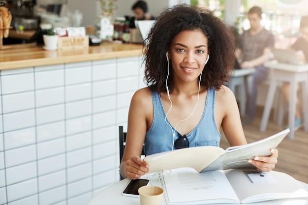 Estudante de mulher africana bonita jovem em fones de ouvido, sentado no café sorrindo segurando o livro. educação e aprendizagem.