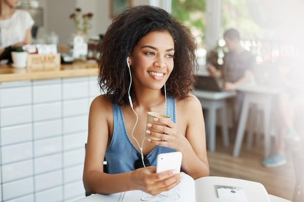 Estudante de mulher africana bonita jovem ouvindo música em fones de ouvido, sorrindo, sentado à mesa com livros no café.