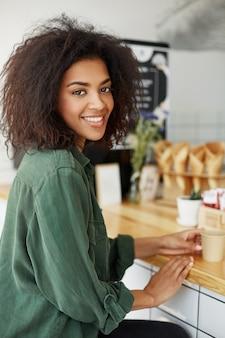Estudante de mulher africana bonita jovem sentado no café sorrindo bebendo café.