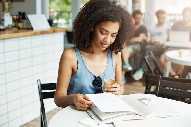 Estudante de mulher africana bonita jovem sentado no café sorrindo olhando revista bebendo café. aprendizagem e educação.