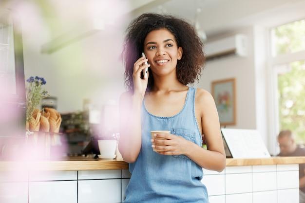 Estudante de mulher africana jovem alegre bonita sorrindo falando no telefone, bebendo café no café.