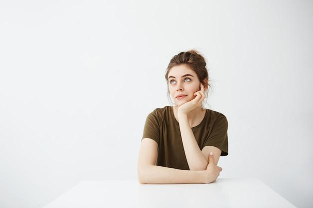 Estudante de mulher bonita nova sonhadora que senta-se na tabela que sonha o pensamento sobre o fundo branco.