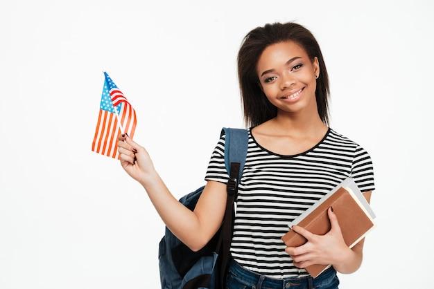 Estudante de mulher com mochila segurando livros e bandeira dos eua