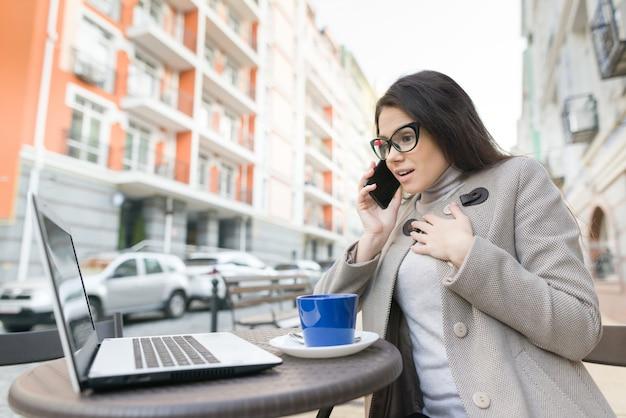 Estudante de mulher com óculos no café ao ar livre com laptop
