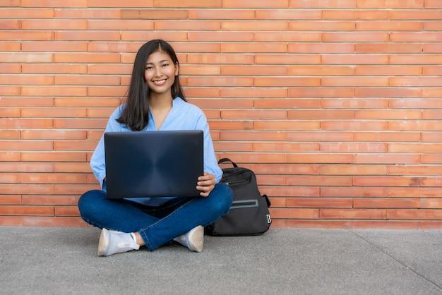 Estudante de mulher de sorriso asiático que senta e que usa o portátil no fundo do tijolo no terreno. estudante adolescente feliz do ensino médio ao ar livre.