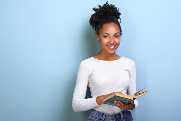 Estudante de mulher do mulato que guarda o livro em sua mão e estudo. de volta à escola .