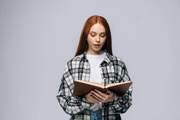 Estudante de mulher jovem e atraente vestindo roupas casuais lendo livro sobre fundo cinza isolado