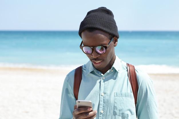 Estudante de pele escura bonito no desgaste da moda, passar o tempo livre depois da faculdade à beira-mar, tendo um agradável passeio pela praia, enviando mensagens online a amigos. pessoas, estilo de vida e tecnologia moderna