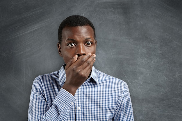 Estudante de pele escura com olhos esbugalhados espantado, vestindo uma camisa xadrez, cobrindo a boca, parecendo chocado e culpado depois de fazer algo errado.