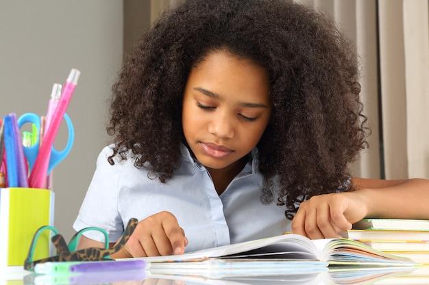 Estudante de pele escura lendo um livro fazendo lição de casa