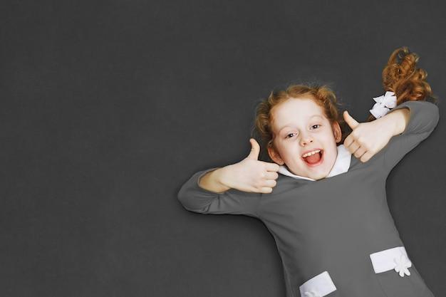 Estudante de riso no vestido cinzento que mostra os polegares que levantam-se perto do quadro-negro.