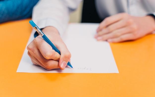 Estudante de segundo grau ou universidade escrevendo em aula teórica.