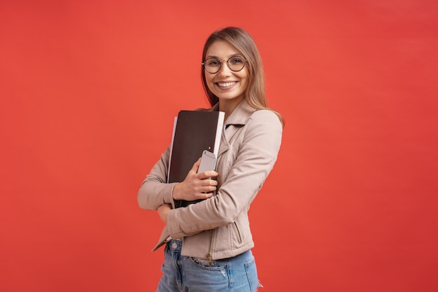 Estudante de sorriso novo ou estagiário nos monóculos que estão com uma pasta na parede vermelha.