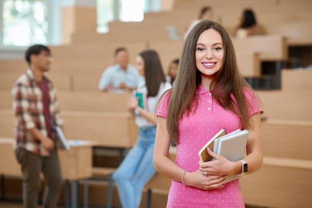 Estudante de sorriso que mantem livros na universidade.