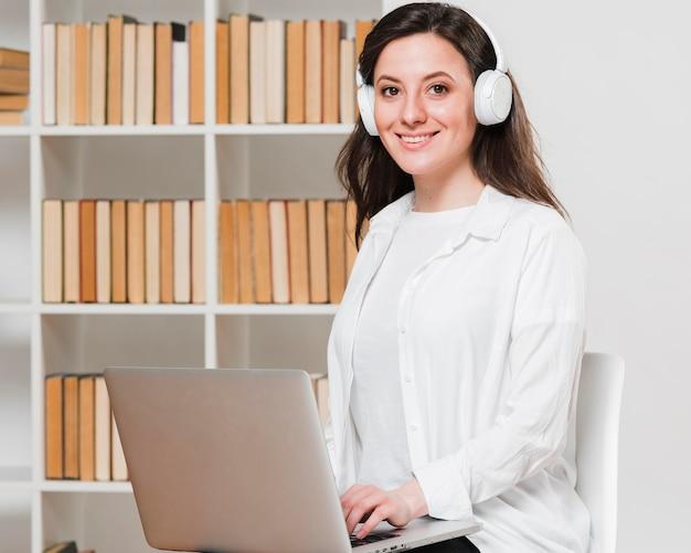 Estudante de tiro médio em um conceito de e-learning de biblioteca