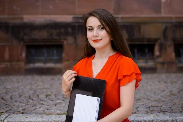 Estudante de vestido vermelho, sentado na frente da antiga universidade convencional