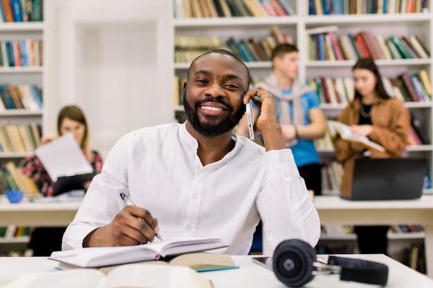 Estudante descasc escuro masculino sorridente, trabalhando em uma biblioteca. estudante universitário, anotando o livro enquanto está sentado na biblioteca e falando ao telefone, sorrindo