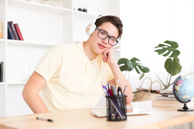 Estudante descontraído sentado em fones de ouvido