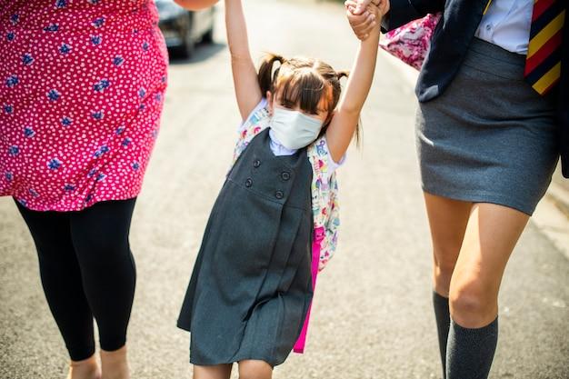 Estudante do ensino médio usando máscaras a caminho de casa