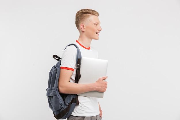 Estudante do sexo masculino 16-18 anos de idade vestindo roupas casuais e mochila andando com segurando o laptop na mão, isolado sobre o branco