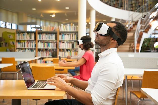 Estudante do sexo masculino adulto com simulador de vr na biblioteca