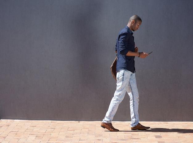Estudante do sexo masculino africano andando com tablet