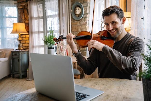 Estudante do sexo masculino aprende a tocar violino online usando um laptop em casa