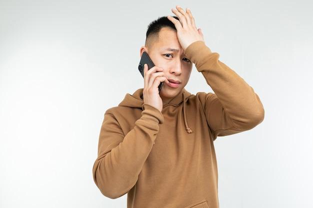 Estudante do sexo masculino asiático elegante bonito falando ao telefone sobre um fundo cinza studio