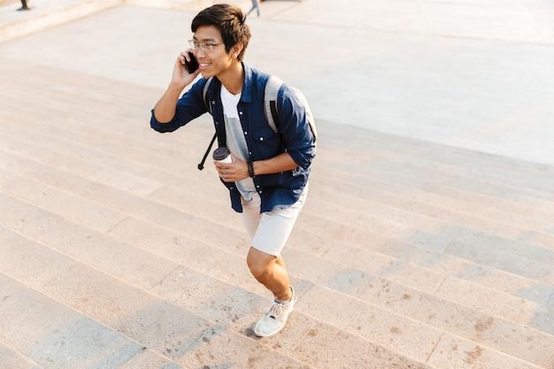 Estudante do sexo masculino asiático satisfeito em óculos falando pelo smartphone enquanto caminhava nas escadas ao ar livre