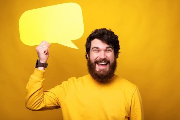 Estudante do sexo masculino barbudo está segurando um discurso de bolha na cabeça.